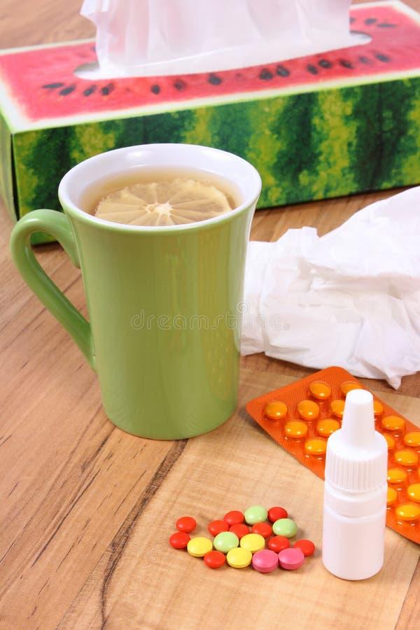 药片和滴鼻剂寒冷、手帕和热的茶的用柠檬 免版税库存照片