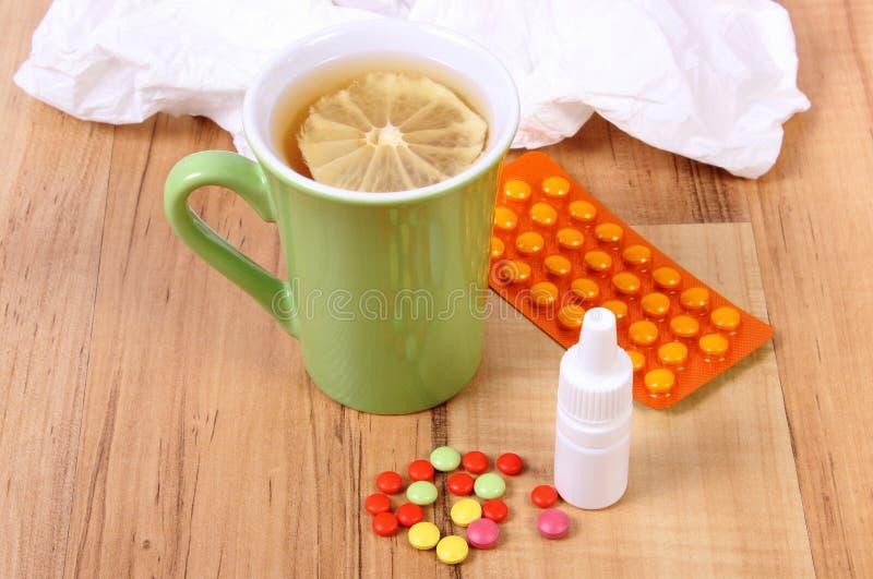 药片和滴鼻剂寒冷、手帕和热的茶的用柠檬 库存照片