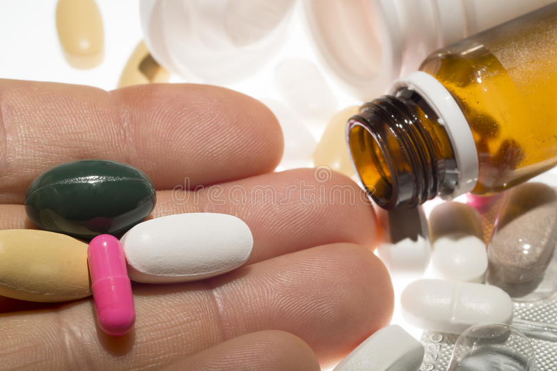 药片在手中有药物背景 免版税库存照片
