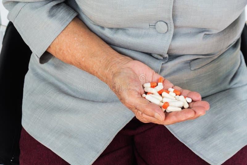 药片在手中,坐椅子和拿着药片的资深妇女我 图库摄影