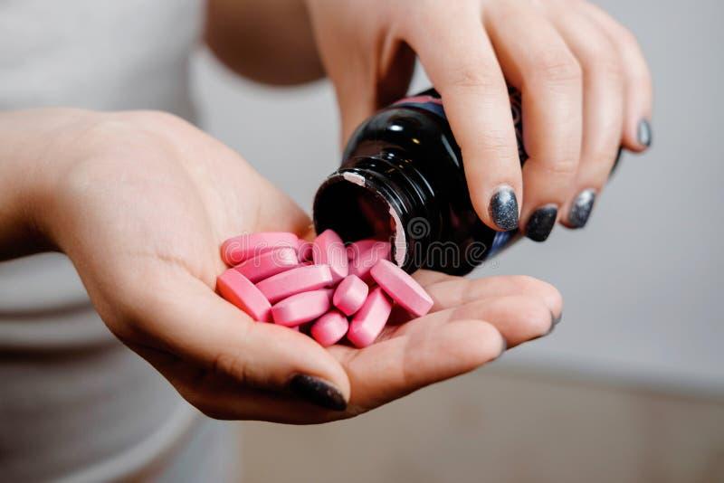 药片在手中,桃红色维生素 免版税库存照片