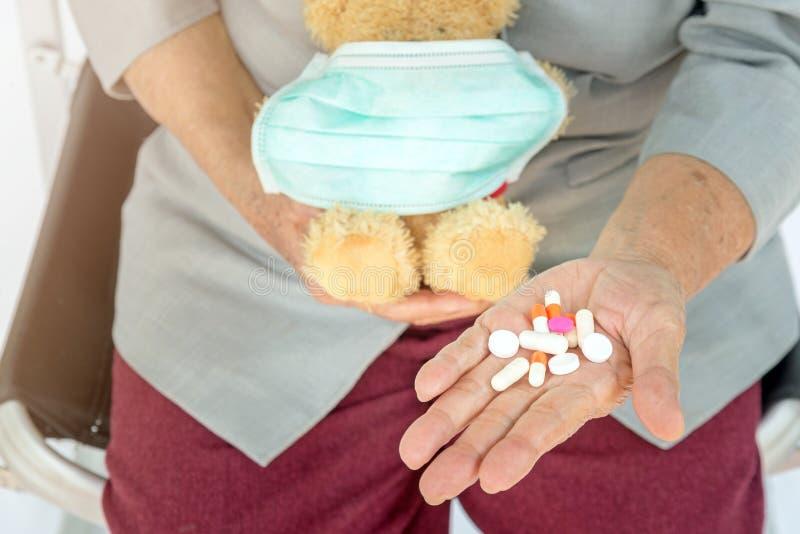 药片在资深妇女手和拿着上与面具的玩具熊在f 图库摄影