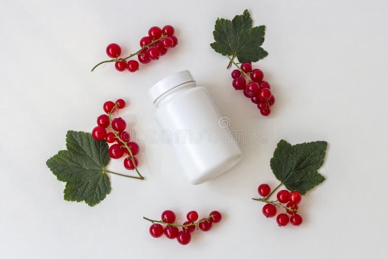 药片或维生素膳食补充剂的白色医学瓶在白色背景的莓果中 免版税图库摄影