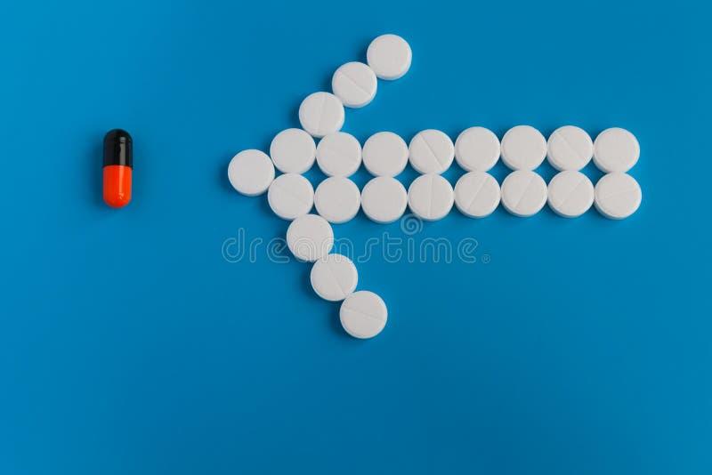 药片白色圆的疗程被计划以箭头的形式指向黑色色的药片用桔子 库存图片