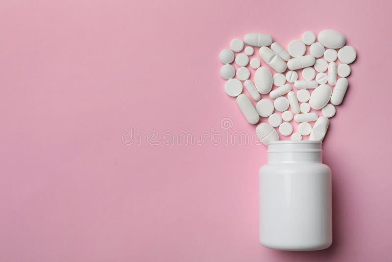 药片的瓶和心脏在颜色背景,平的位置的 免版税图库摄影