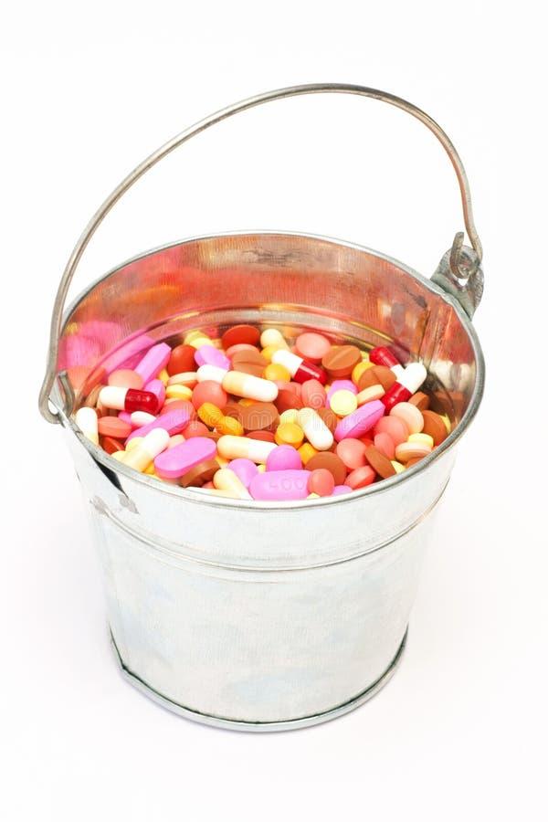 药片,在一个桶的胶囊在白色背景,药房,医学 免版税库存照片