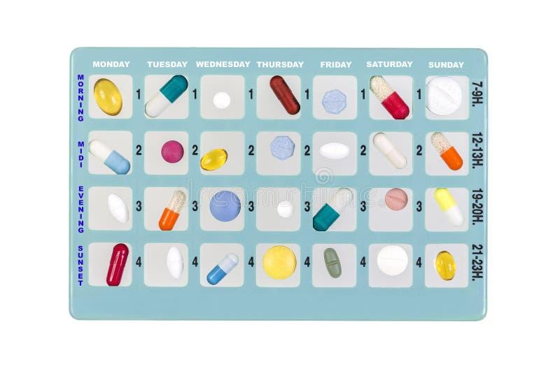 药物存贮的蓝色药片箱子,与星期的片刻的题字在白色的 免版税库存照片