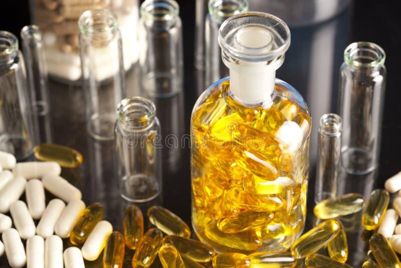药物或膳食补充剂和倒空医疗容器 库存照片
