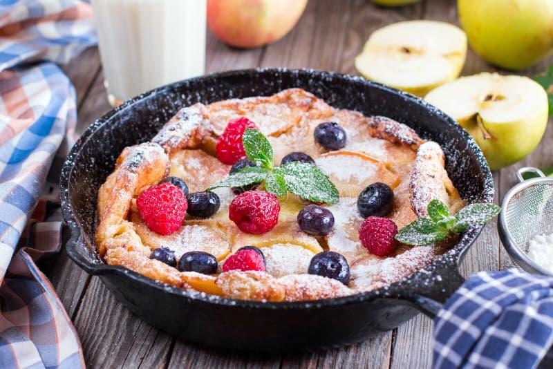荷兰婴孩薄煎饼用苹果和桂香和新鲜的蓝莓 免版税库存照片