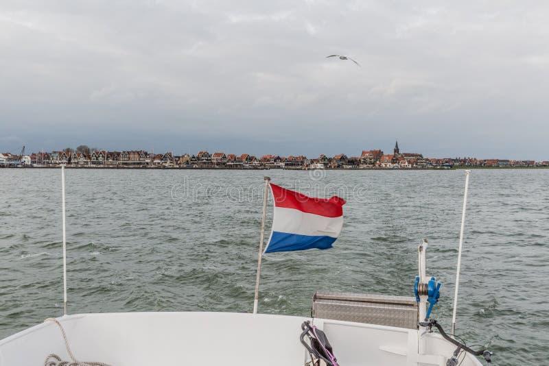 荷兰的旗子一条小船的船尾的有福伦丹的在背景中 免版税库存照片