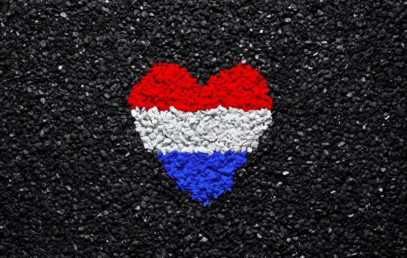 荷兰的旗子,在黑背景、石头、石渣和木瓦,墙纸的心脏 免版税图库摄影