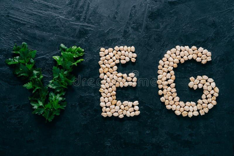 荷兰芹和干鹰嘴豆以意味veg,素食主义者的信件的形式被隔绝在黑暗的背景 有机蛋白质产品 r 库存图片