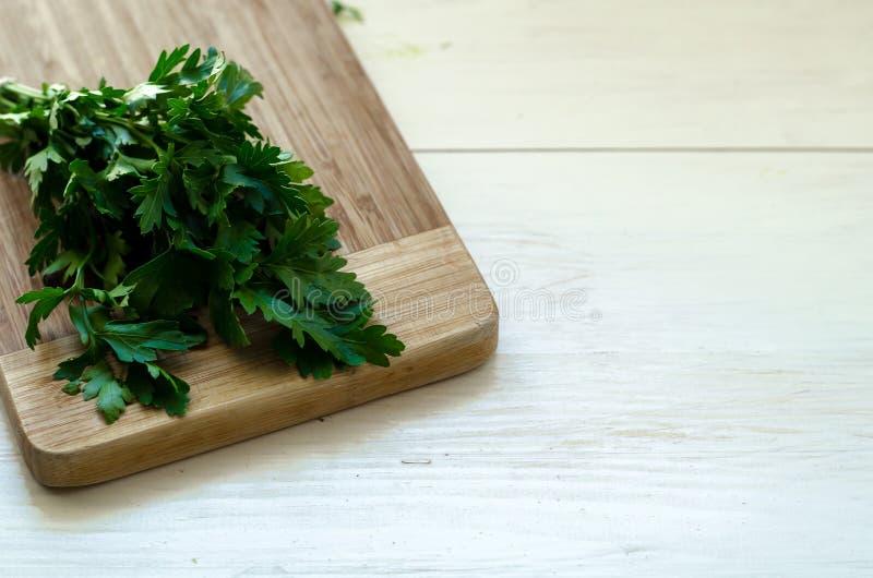 荷兰芹和莳萝在切板,木背景 免版税库存图片