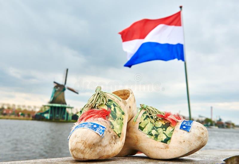 荷兰 木鞋子netherland旗子和风车在zaanse schans 免版税库存图片