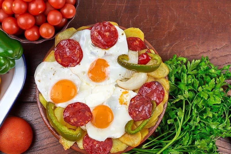 荷包蛋、加调料的口利左香肠、油煎的土豆、青椒和葱 免版税图库摄影