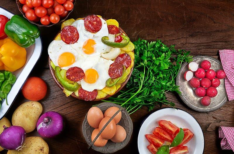 荷包蛋、加调料的口利左香肠、油煎的土豆、青椒和葱 免版税库存图片