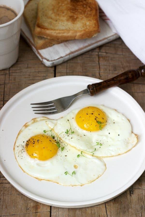 荷包蛋、面包多士和咖啡早餐在一张木桌上 土气样式 库存图片