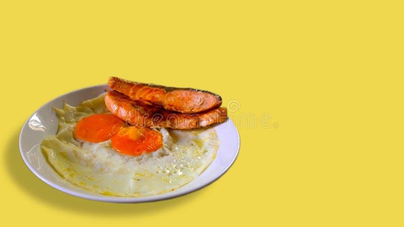 荷包蛋和三文鱼在一块白色板材有黄色背景 免版税库存照片