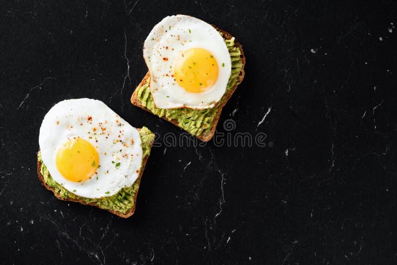 荷包蛋和被捣碎的鲕梨在烤面包片 库存照片