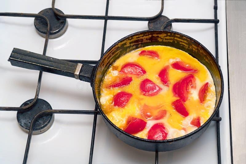 荷包蛋用在一个平底锅的蕃茄在煤气炉 免版税库存照片