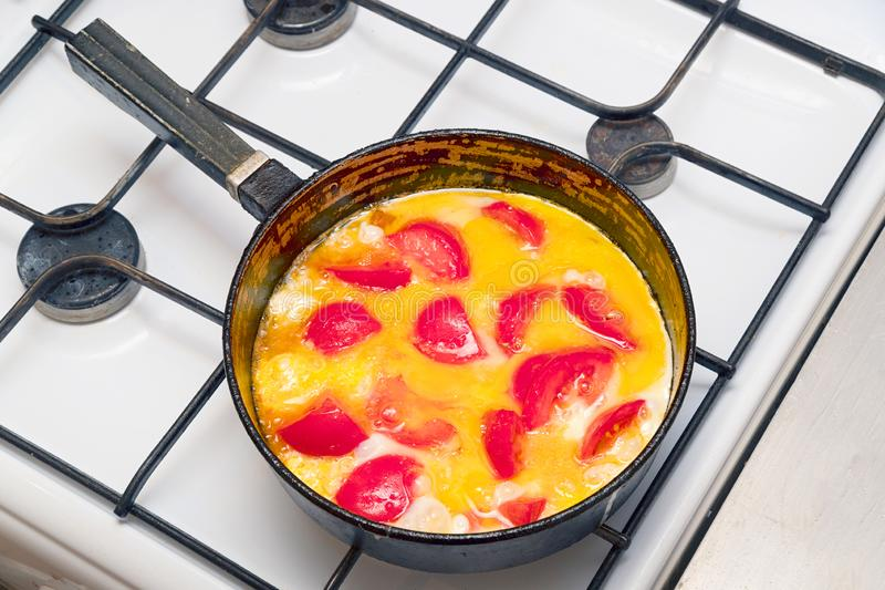 荷包蛋用在一个平底锅的蕃茄在煤气炉 免版税库存图片