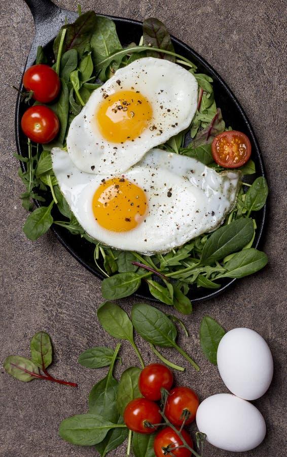 荷包蛋用新鲜的草本和西红柿在平底锅在棕色背景 免版税图库摄影