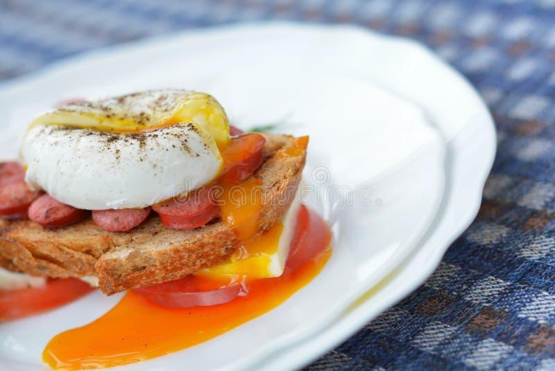 荷包蛋连续卵黄质在三明治的用香肠,面包,乳酪,在接近白色板材的蕃茄 免版税图库摄影