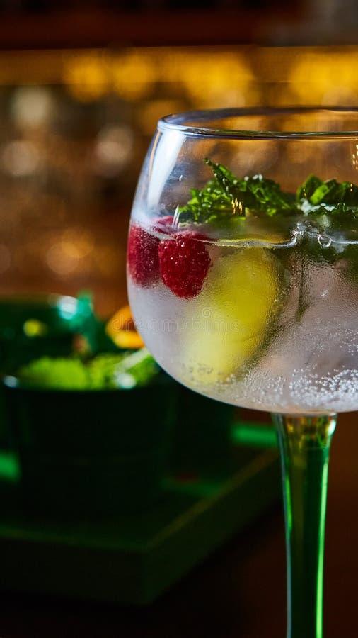 莓与石灰和新鲜薄荷的Mojito柠檬水在木背景的玻璃 库存照片