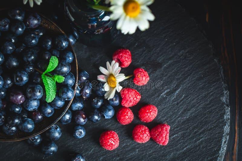 莓和蓝莓与春黄菊和叶子在黑暗的背景 夏天和健康食品概念 r 免版税图库摄影