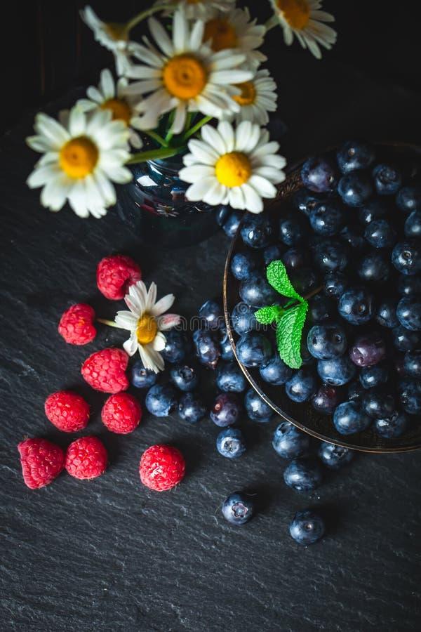 莓和蓝莓与春黄菊和叶子在黑暗的背景 夏天和健康食品概念 r 库存照片