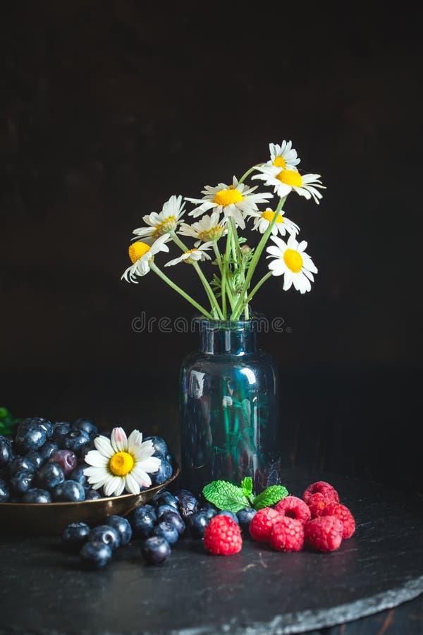 莓和蓝莓与春黄菊和叶子在黑暗的背景 夏天和健康食品概念 ?? 库存照片