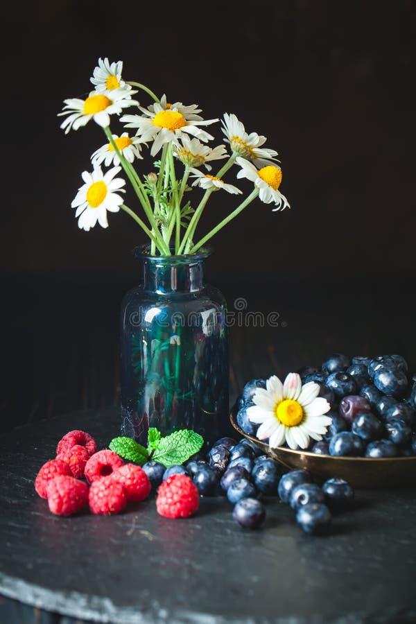 莓和蓝莓与春黄菊和叶子在黑暗的背景 夏天和健康食品概念 ?? 库存图片