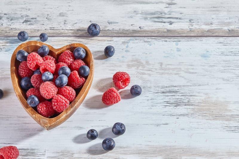 莓和蓝莓在一个木心形的碗在白色土气木背景 r 库存照片