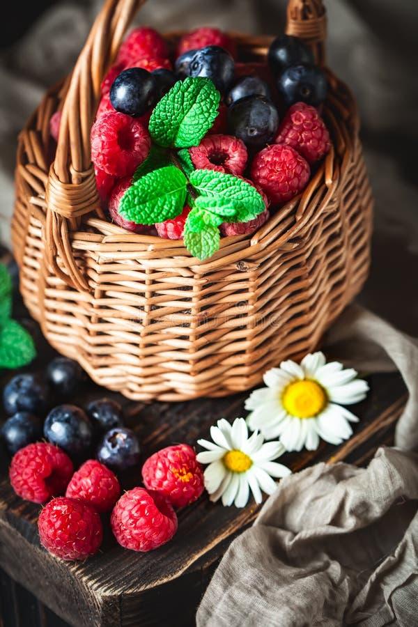 莓和蓝莓在一个篮子与春黄菊和叶子在黑暗的背景 夏天和健康食品概念 免版税库存图片
