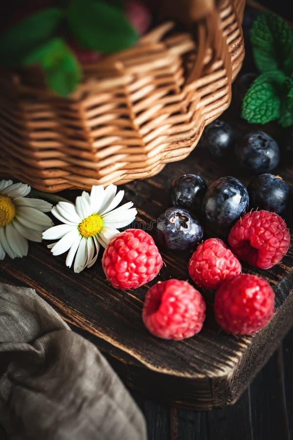 莓和蓝莓在一个篮子与春黄菊和叶子在黑暗的背景 夏天和健康食品概念 免版税库存照片