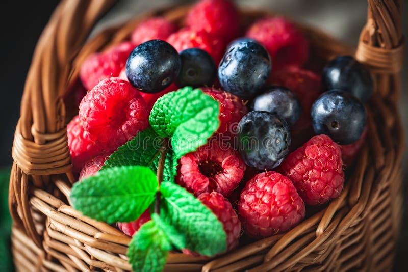 莓和蓝莓在一个篮子与春黄菊和叶子在黑暗的背景 夏天和健康食品概念 库存照片
