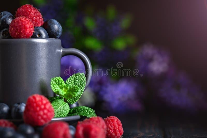 莓和蓝莓在一杯在黑暗的背景 夏天和健康食品概念 r 免版税库存图片
