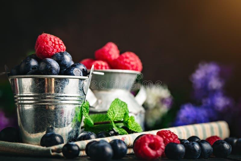 莓和蓝莓在一杯在黑暗的背景 夏天和健康食品概念 r 库存照片