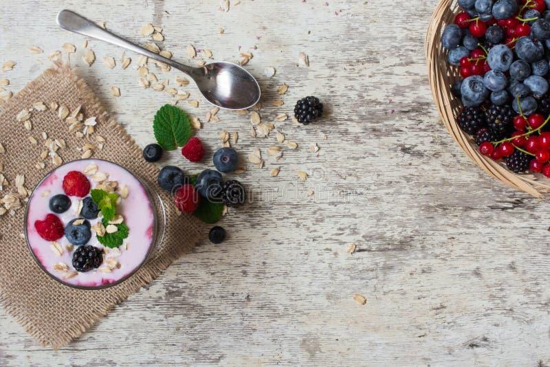 莓果圆滑的人用燕麦粥、薄菏和匙子在玻璃 顶视图 健康的早餐 免版税库存图片