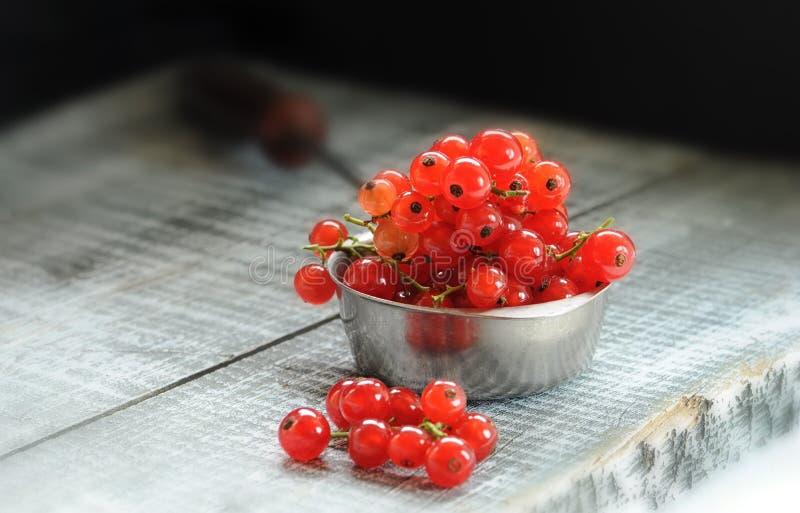 莓果成熟红浆果在一把金属匙子的一个木板说谎在光柱 库存照片