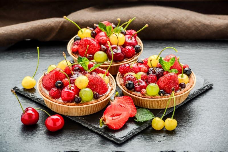 莓果果子馅饼用蓝莓,莓,猕猴桃,草莓,杏仁在糖粉剥落 免版税库存图片