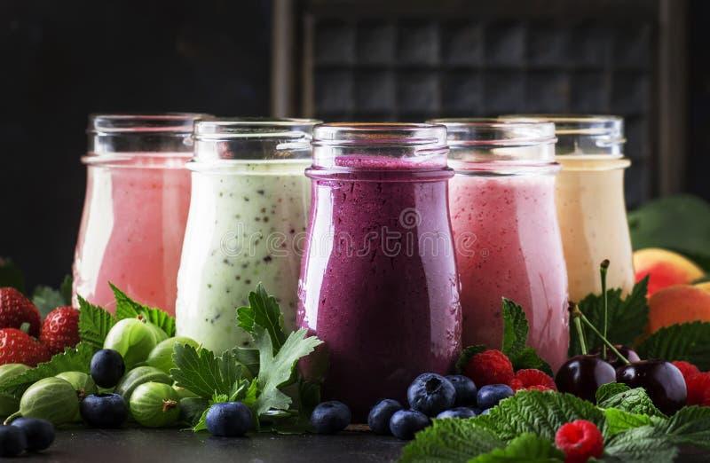 莓果cokctalis、圆滑的人和奶昔、新鲜水果和莓果在棕色桌,静物画,选择聚焦上 免版税库存图片