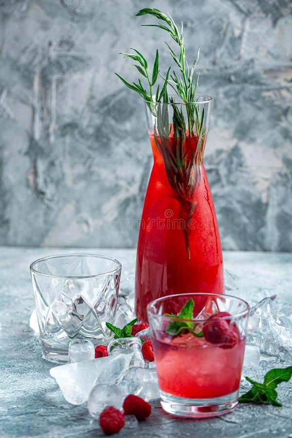 莓鸡尾酒,嘶嘶响,柠檬水,冰茶用在蓝色木背景的新鲜薄荷 ?? 免版税库存照片
