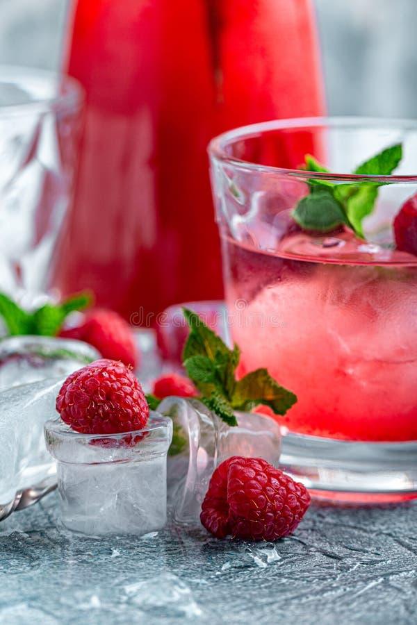 莓鸡尾酒,嘶嘶响,柠檬水,冰茶用在蓝色木背景的新鲜薄荷 ?? 免版税库存图片
