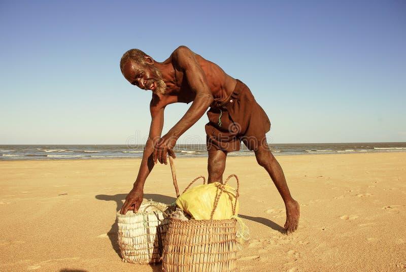 莫三鼻克索法拉比拉市 — 2006年7月23日:阳光明媚的日子里,一名非洲渔民在沙滩上微笑,沙子里放着草篮 库存照片