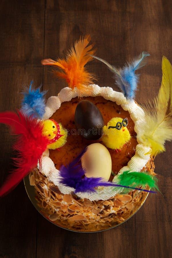 莫娜de pascua,在复活节的西班牙星期一吃的蛋糕的特写镜头,装饰与羽毛和一只女用连杉衬裤小鸡在土气 库存照片