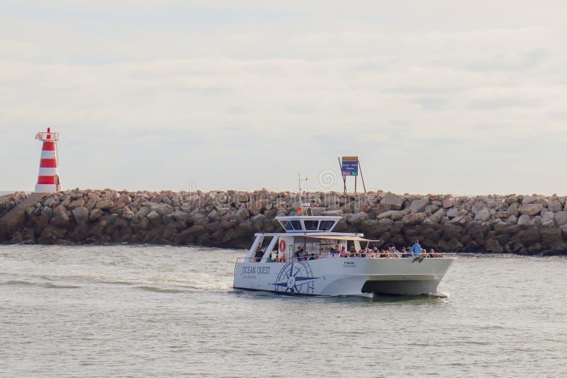 莫拉镇,葡萄牙-到达有游人的小游艇船坞的游览小船甲板的 免版税图库摄影