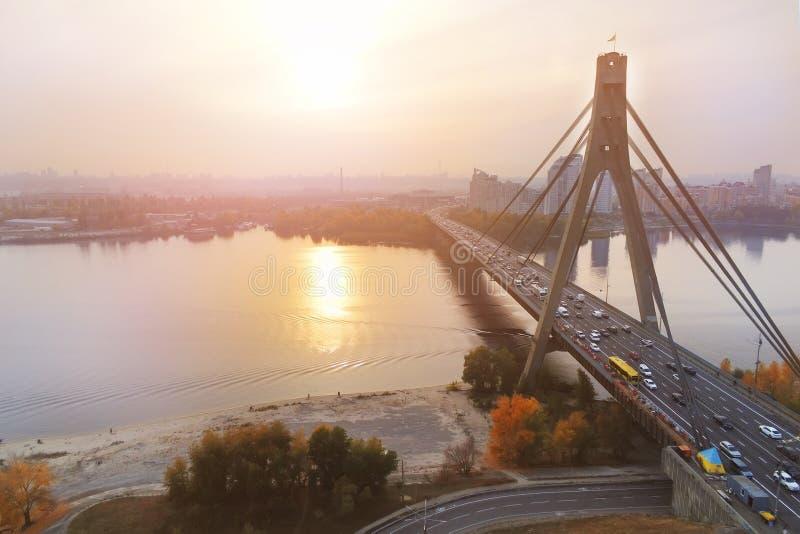 莫斯科桥梁在平衡时间的日落的基辅 乌克兰首都都市风景 在路的交通 空中寄生虫视图 免版税库存图片