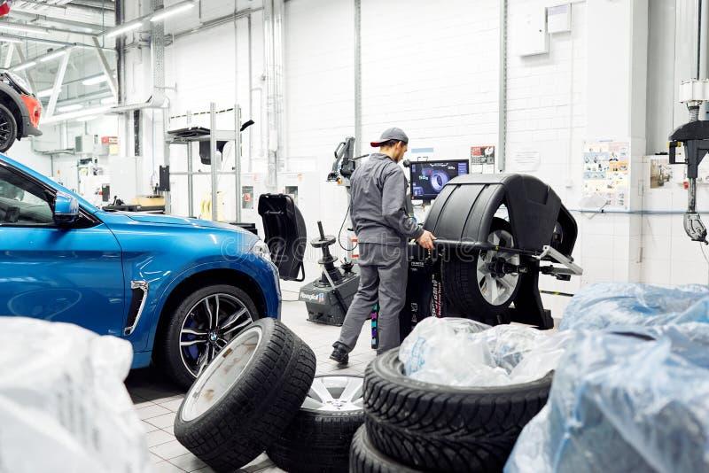 莫斯科,俄罗斯, 09 06 2018年:人在平衡的机器的轮胎检查 免版税库存照片