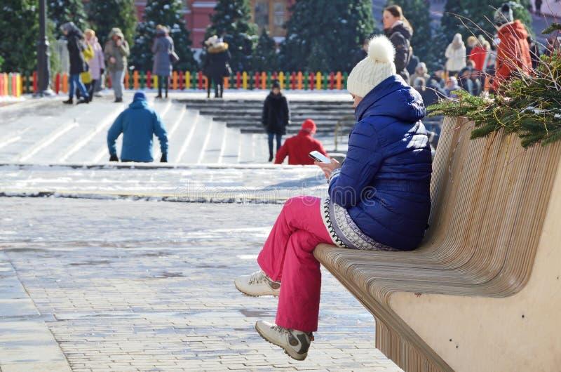 莫斯科,俄罗斯, 2018年3月, 06日 运动服的妇女有手机的坐在Manezhnaya广场的一条长凳在莫斯科 免版税库存图片